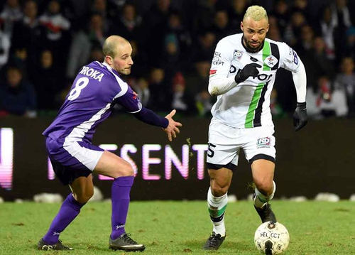 Photo: OH Leuven midfielder John Bostock (right) glides past an opponent in the Belgium top flight. (Courtesy Touchline Talk)