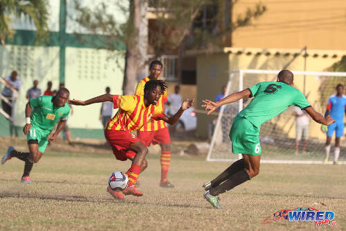 "Photo: Point Fortin Civic midfielder Akeem Redhead (centre) runs at San Juan Jabloteh left back Akeem ""Battery"" Benjamin (right) during TT Pro League action at the Barataria Recreation Ground, Barataria on 5 March 2016. (Courtesy Chevaughn Christopher/Wired868)"