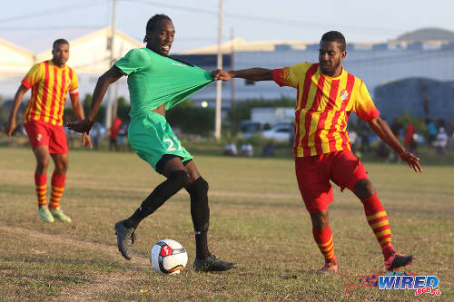 Photo: Point Fortin Civic left back Shaquille Stewart tries to help himself to the shirt of San Juan Jabloteh winger Nathan Lewis during TT Pro League action at the Barataria Recreation Ground, Barataria on 5 March 2016. (Courtesy Chevaughn Christopher/Wired868)
