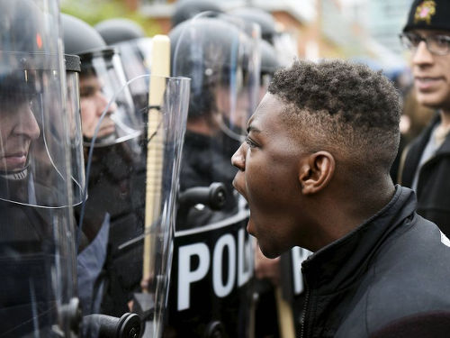 Photo: A protester makes his point to lawmen during demonstrations in Baltimore after the killing of Freddie Gray. (Copyright Sowetanlive.co.za)