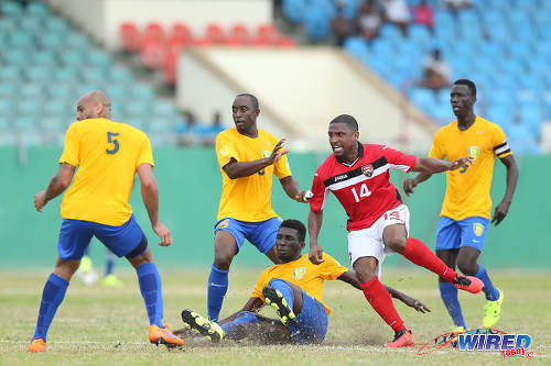 Photo: Trinidad and Tobago midfielder Andre Boucaud (centre) is surrounded by four St Vincent and the Grenadines players during Russia 2018 World Cup qualifying action at Arnos Vale on 25 March 2016. Trinidad and Tobago won 3-2. (Courtesy Allan V Crane/CA-images/Wired868)