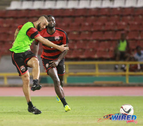 Photo: Trinidad and Tobago midfielder John Bostock (left) strikes the ball during national practice while team captain Kenwyne Jones look on at the Hasely Crawford Stadium on 21 March 2016. (Courtesy Nicholas Bhajan/Wired868)