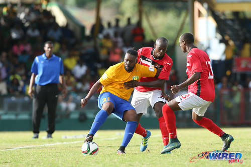 Photo: St Vincent and the Grenadines attacker David Pitt (left) holds off Trinidad and Tobago defender Daneil Cyrus (centre) while teammate Justin Hoyte looks on during Russia 2018 World Cup qualifying action at Arnos Vale on 25 March 2016. Trinidad and Tobago won 3-2. (Courtesy Allan V Crane/CA-images/Wired868)