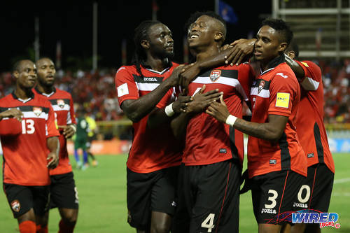 Photo: Trinidad and Tobago defender Sheldon Bateau (centre) is congratulated by teammates after grabbing the opening goal in a 6-0 win over St Vincent and the Grenadines at the Hasely Crawford Stadium, Port of Spain on 29 March 2016. (Courtesy: Allan V Crane/CA-images/Wired868)