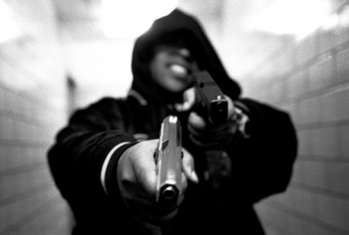 Photo: A hooded thug shows off his weapons. (Courtesy Wehearit.com)