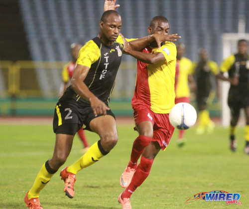 Photo: Defence Force defender Glen Franklin (left) holds off North East Stars forward Kerry Baptiste during Pro League on 19 April 2016 at the Hasely Crawford Stadium. Baptiste scored the winner as Stars won 1-0. (Courtesy Nicholas Bhajan/Wired868)