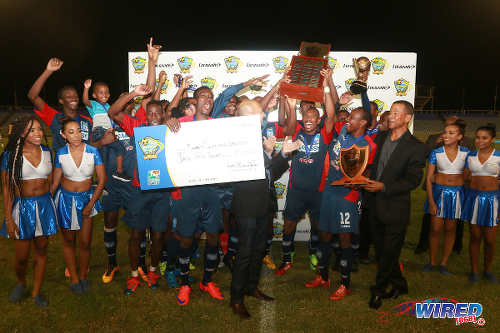 Photo: Morvant Caledonia United players celebrate with the winning trophy and cheque after defeated W Connection in the Lucozade Sport Goal Shield final on 21 April 2016. Looking on (far right) is Pro League CEO Dexter Skeene. (Courtesy Nicholas Bhajan/Wired868)