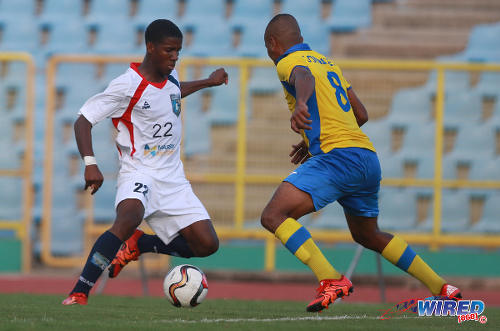 Photo: Morvant Caledonia United utility player Jameel Neptune (left) takes on Defence Force player Curtis Gonzales during Lucozade Sport Goal Shield quarterfinal action on 9 April 2016. (Courtesy Nicholas Bhajan/Wired868)