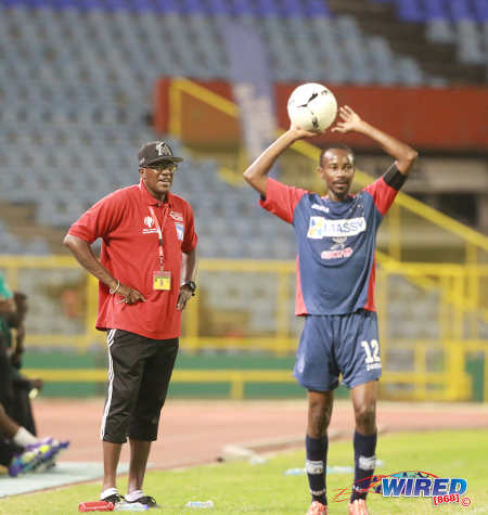 "Photo: Morvant Caledonia United coach Jerry Moe (left) looks on as team captain Kareem ""Tiny"" Joseph prepares to take a throw during the Lucozade Sport Goal Shield final against W Connection on 24 April 2016. Caledonia won 4-1 on kicks from the penalty mark. (Courtesy Nicholas Bhajan/Wired868)"
