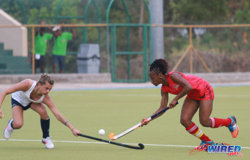Photo: Trinidad and Tobago captain Kayla Brathwaite (right) dribbles past a United States opponent during their opening fixture of the 2016 Women's Junior Pan American Championship in Tacarigua on Thursday 31 March 2016. (Courtesy Nicholas Bhajan/Wired868)