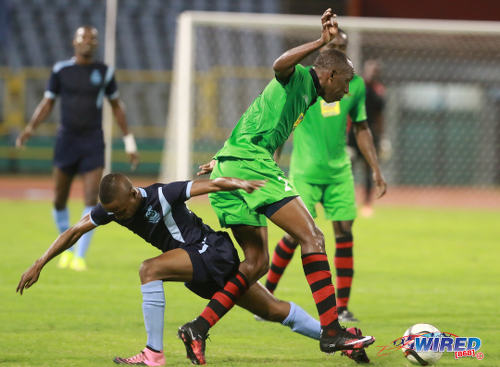 Photo: San Juan Jabloteh full back Noel Williams (right) takes on Police FC flanker Clevon McFee during Lucozade Sport Goal Shield quarterfinal action on 9 April 2016. Police won 3-0. (Courtesy Nicholas Bhajan/Wired868)