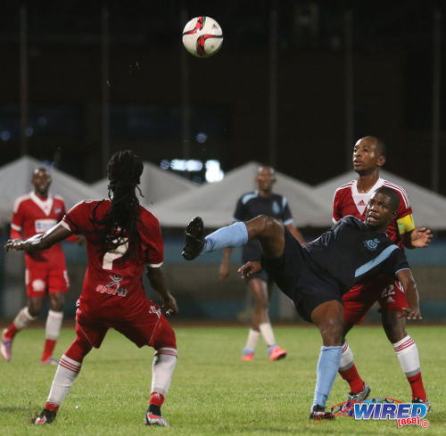Photo: Police FC midfielder Kaaron Foster (centre) keeps his eye on the ball while Central FC players Leston Paul (right) and Jason Marcano look on during TT Pro League action on 2 April 2016. Police FC won 1-0. (Courtesy Chevaughn Christopher/CA-images/Wired868)