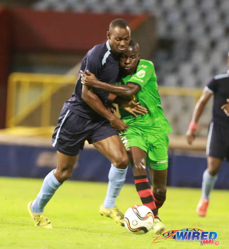 Photo: San Juan Jabloteh midfielder Fabian Reid (right) tries to hold on to Police FC forward Keon Wilson during Lucozade Sport Goal Shield quarterfinal action on 9 April 2016. Police won 3-0. (Courtesy Nicholas Bhajan/Wired868)