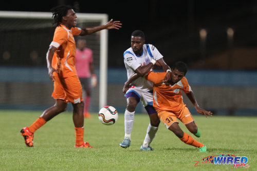 Photo: St Ann's Rangers attacker Johan Peltier (centre) wrestles with Club Sando midfielder Michael Basdeo (right) while his teammate Moron Phillip appeals to the referee during Lucozade Sport Goal Shield qualifying action on 5 April 2016 at the Ato Boldon Stadium, Couva (Courtesy Chevaughn Christopher/CA-images/Wired868)
