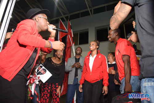 "Photo: Trinidad and Tobago gymnast Thema Williams (centre) is serenaded by 2016 International Soca Monarch Aaron ""Voice"" St Louis at the Piarco International Airport on her return from Rio welcomed home from Rio on Wednesday 20 April 2016. Looking on are Williams' parents, Leon Williams (right) and Helen Adams (second from left). (Courtesy Wired868)"