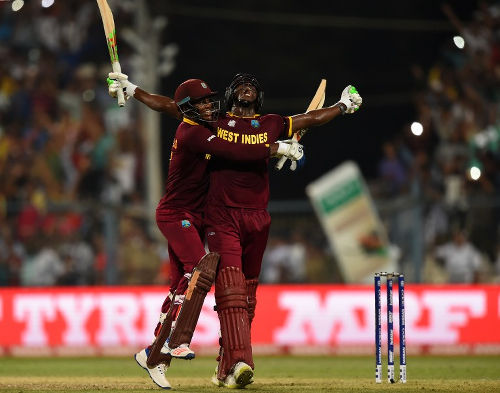 Photo: West Indies' Carlos Brathwaite (right) and teammate Marlon Samuels celebrate after victory in the World T20 cricket tournament final match between England and West Indies at The Eden Gardens Cricket Stadium in Kolkata on 3 April 2016. (Copyright AFP 2016/Dibyangshu Sarkar)