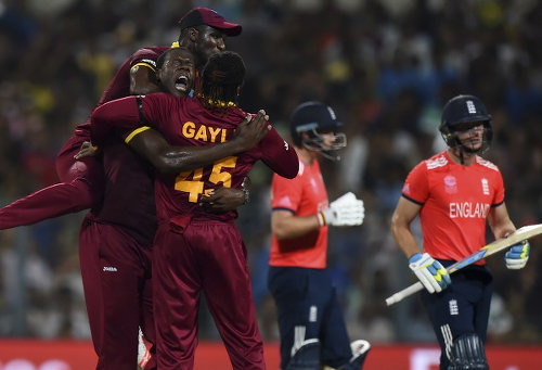 Photo: West Indies bowler Carlos Brathwaite (second from left) celebrates with captain Darren Sammy (top) and Chris Gayle after the wicket of England's Jos Buttler (far right) during the World T20 cricket tournament final match at The Eden Gardens Cricket Stadium in Kolkata on 3 April 2016. Carlos Brathwaite sensationally hit four successive sixes off Ben Stokes in the last over as the West Indies stunned England by four wickets to win the World Twenty20 title. (Copyright AFP2016/Dibyangshu Sarkar)