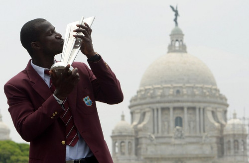 Photo: West Indies' captain Darren Sammy poses with the World T20 cricket tournament trophy one day after West Indies won the event in the Indian city of Kolkata on 4 April 2016. (Copyright AFP 2016/Dibyangshu Sarkar)
