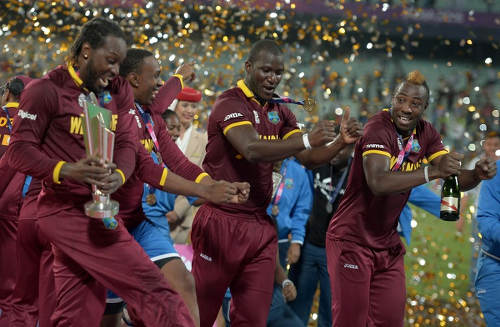 Photo: West Indies cricket players (from left) Chris Gayle, Dwayne Bravo, Darren Sammy and Andre Russell celebrate their World T20 cricket tournament final win over England at The Eden Gardens Cricket Stadium in Kolkata on 3 April 2016. Carlos Brathwaite sensationally hit four successive sixes off Ben Stokes in the last over as the West Indies stunned England by four wickets to win the World Twenty20 title. (Copyright AFP2016/Dibyangshu Sarkar)
