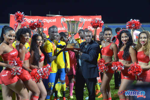 Photo: Defence Force captain Jerwyn Balthazar (centre) takes the Digicel Pro Bowl trophy after their 2-1 win over W Connection on 27 May 2016. (Courtesy Chevaughn Christopher/Wired868)