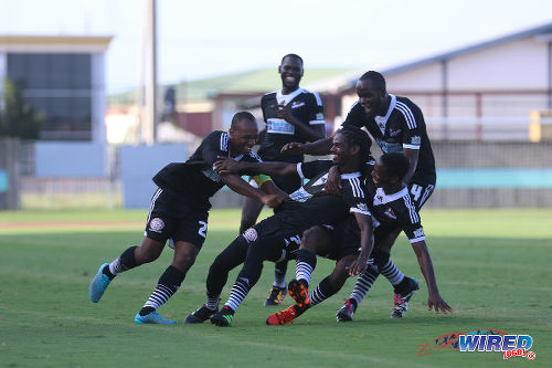 Photo: Central FC forward Jason Marcano (centre) is dragged to the ground by his teammates after his opening goal against North East Stars at the Mannie Ramjohn Stadium in Marabella on 8 May 2016. Marcano scored twice as Central cruised to a 4-0 to complete their successful defence of the league title. (Courtesy Chevaughn Christopher/Wired868)