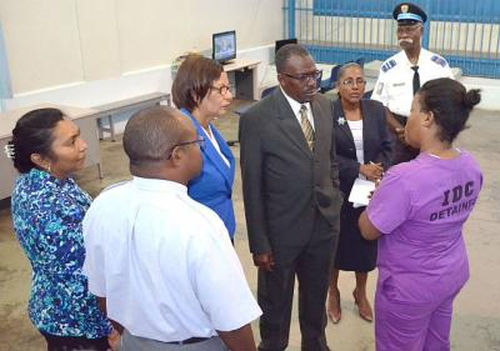 Photo: National Security Minister Brigadier Edmund Dillon (centre) speaks to a female detainee at the Immigration Detention Centre.