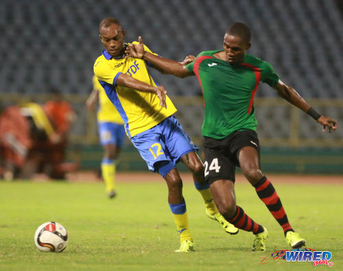 Photo: San Juan Jabloteh defender Adrian Reid (right) tries to hold off Defence Force winger Jemel Sebro during 2016 Pro Bowl semifinal action on May 13 at the Hasely Crawford Stadium on Port of Spain. (Courtesy Nicholas Bhajan/Wired868)
