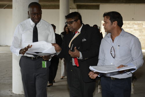 Photo: Minister of Communications and Public Administration Maxie Cuffie (far left) on a tour of the incomplete Chaguanas Library. (Courtesy Ministry of Communications)