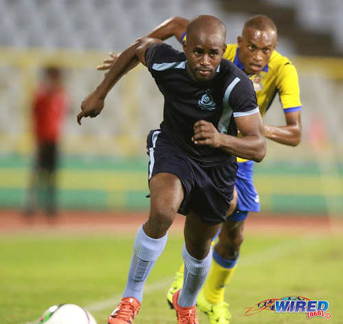 Photo: Police FC left back Dexter Alleyne tries to outrun Defence Force flanker Jemel Sebro during Pro League action at the Hasely Crawford Stadium on 3 May 2016. Defence Force won 3-2. (Courtesy Nicholas Bhajan/Wired868)