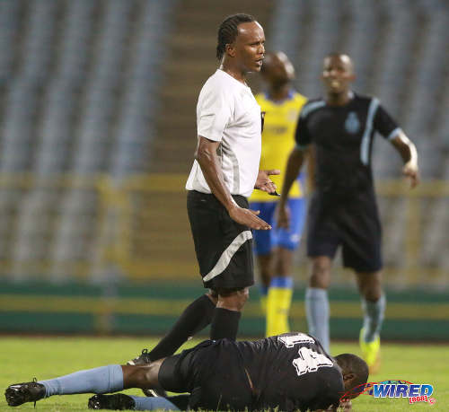 Photo: Referee Marlon Peruse (centre) stands over Police FC stand-in captain Kaaron Foster during Pro League action at the Hasely Crawford Stadium on 3 May 2016. Defence Force won 3-2. (Courtesy Nicholas Bhajan/Wired868)