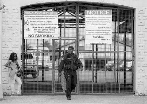 Photo: A police office leaves a Trinidad and Tobago prison. (Copyright Trinidad Guardian)