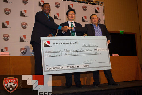 Photo: TTFA president David John-Williams (left) shakes hands with a Shanghai Group of Companies representative on a TT$600,000 deal to play China. (Courtesy TTFA Media)