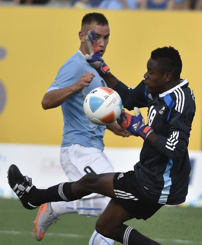Photo: Trinidad and Tobago National Under-23 goalkeeper Javon Sample (right) denies Uruguay attacker Junior Arias during the Pan American Games in Hamilton, Canada, on 13 July 13 2015. (Copyright AFP 2016/Omar Torres)