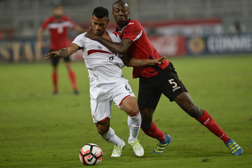 Photo: Trinidad and Tobago defender Daneil Cyrus (right) grapples with Peru full back Miguel Trauco during a friendly international at the National stadium in Lima on 23 May 2016.  Peru won 4-0. Cyrus will miss Friday's contest with Uruguay through injury. (Copyright Ernesto Benavides/AFP 2016)