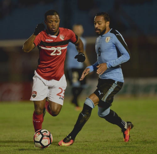 Photo: Trinidad and Tobago midfielder Jomal Williams (left) takes the ball past Uruguay defender Alvaro Pereira during friendly international action at the Centenario Stadium in Montevideo on 27 May 2016. Uruguay won 3-1. (Copyright Miguel Rojo/AFP 2016)