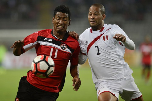Photo: Trinidad and Tobago striker Willis Plaza (left) tries to keep the ball from Peru defender Alberto Rodriguez during international friendly action at the National stadium in Lima on 23 May 2016. (Copyright Ernesto Benavides/AFP 2016/Wired868)