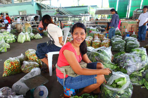 Photo: A young woman sells at the market.