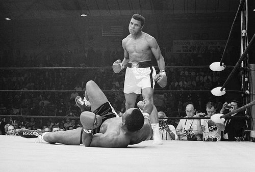 Photo: Muhammad Ali (right), then Cassius Clay, glares at fallen heavyweight champion Sonny Liston. (Copyright Entrepello.com)