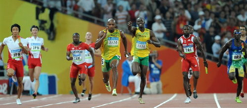 Photo: Trinidad and Tobago sprinter Richard Thompson (third from right) prepares to chase Jamaica star Asafa Powell (centre), as he receives the baton from Usain Bolt at the Beijing 2008 Olympic Games.