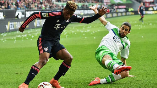 Photo: Bayern Munich winger and France international Kingsley Coman (left) takes on a Vfl Wolfsburg defender during Bundesliga action. (Copyright ESPN)