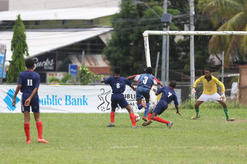 Photo: Malabar Young Stars attacker Jorel Grant (centre) squeezes between Mafeking United players Tamaar Williams (second from left) and Kirby Stewart (second from right) while goalkeeper Marc Mahabir gets ready during Republic Bank National Youth League action on 11 June 2016. (Courtesy Chevaughn Christopher/All Sport)
