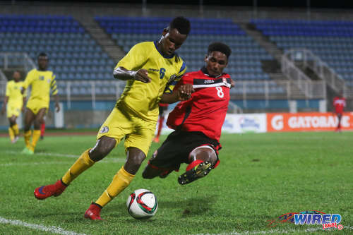 Photo: Trinidad and Tobago National Under-20 winger Jarred Dass (right) tackles St Lucia defender Melvin Doxilly during 2016 Caribbean Cup qualifying action at the Ato Boldon Stadium on 19 June 2016. The two teams played to a 1-1 draw. (Courtesy Chevaughn Christopher/Wired868)