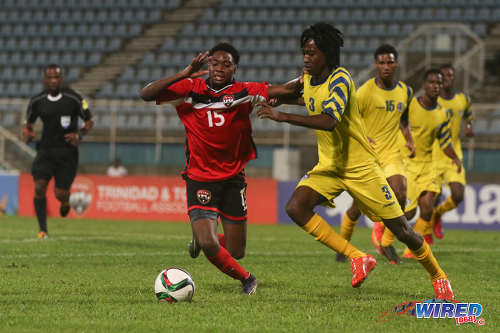 Photo: Trinidad and Tobago National Under-20 winger Kathon St Hillaire (left) is closed down by St Lucia left back Keeroy Lionel during 2016 Caribbean Cup qualifying action at the Ato Boldon Stadium on 19 June 2016. The two teams played to a 1-1 draw. (Courtesy Chevaughn Christopher/Wired868)