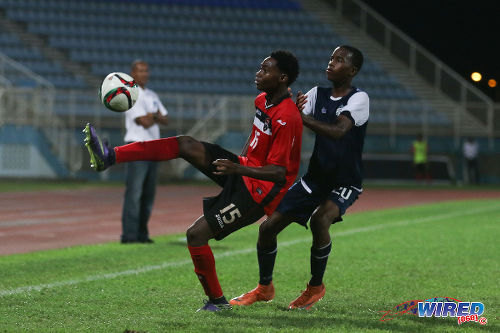 Photo: Trinidad and Tobago National Under-20 midfielder Kathon St Hillaire (left) controls the ball under pressure from Turks and Caicos player Ras Diamond during Caribbean Cup qualifying action at the Ato Boldon Stadium on 17 June 2016. T&T won 11-0. (Courtesy Chevaughn Christopher/Wired868)