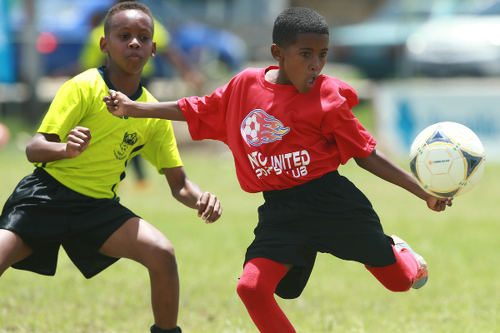 Photo: A Pinto United SC player (right) prepares to strike the ball, despite the attentions of an Adrenaline FA opponent, during Republic Bank National Youth League East Zone Under-12 action on 4 June 2016. Pinto won 4-0. (Courtesy Allan V Crane/CAI Sports/All Sport)