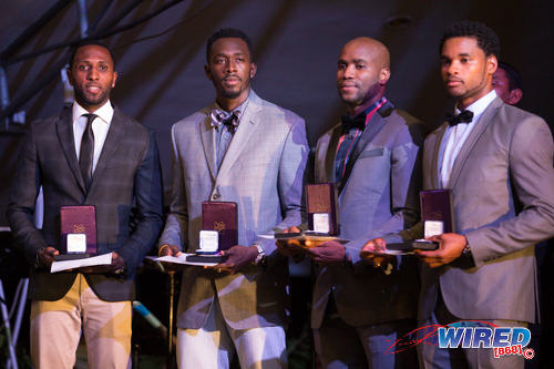 Photo: Done the old talk... Make it rain allyuh! Trinidad and Tobago's 4x100 metre relay team of (from left) Richard Thompson, Marc Burns, Emmanuel Callender and Keston Bledman pose with their London 2012 Olympic Games silver medals in a ceremony at the Anchorage, Carenage on 29 June 2016. (Courtesy Allan V Crane/CA Images/Wired868)