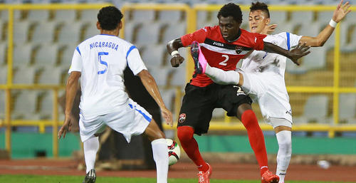 "Photo: Trinidad and Tobago defender Aubrey David (centre) tries to wriggle his way past two Nicaragua opponents during an international friendly fixture on 13 October 2013 at the Hasely Crawford Stadium in Port of Spain. The ""Soca Warriors"" and Nicaragua played to a goalless draw. (Courtesy TTFA Media)"