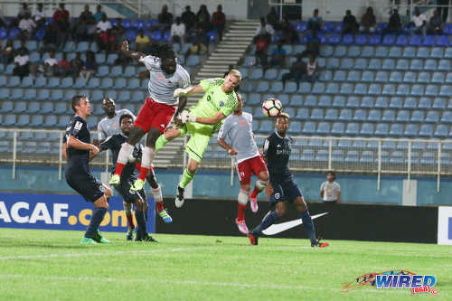 Photo: Central FC forward Kenwyne Jones (centre) heads a free kick past Sporting Kansas City goalkeeper Jon Kempin during CONCACAF Champions League action at the Ato Boldon Stadium in Couva on 16 August 2016. However, the effort was controversially ruled out by the match referee. Jones did score in the match, which ended 2-2. (Courtesy Chevaughn Christopher/Wired868)