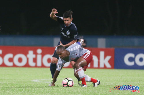 Photo: Central FC captain Leston Paul (right) tries to hold off a Sporting Kansas City opponent during CONCACAF Champions League action at the Ato Boldon Stadium in Couva on 16 August 2016. Both teams played to a 2-2 draw. (Courtesy Chevaughn Christopher/Wired868)