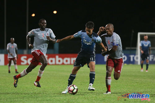 Photo: Central FC captain and midfielder Leston Paul (right) keeps tabs on Vancouver Whitecaps attacker Nicholas Mezquida (centre) while defender Keion Goodridge looks on during CONCACAF Champions League action in Couva on 2 August 2016. (Courtesy Chevaughn Christopher/Wired868)